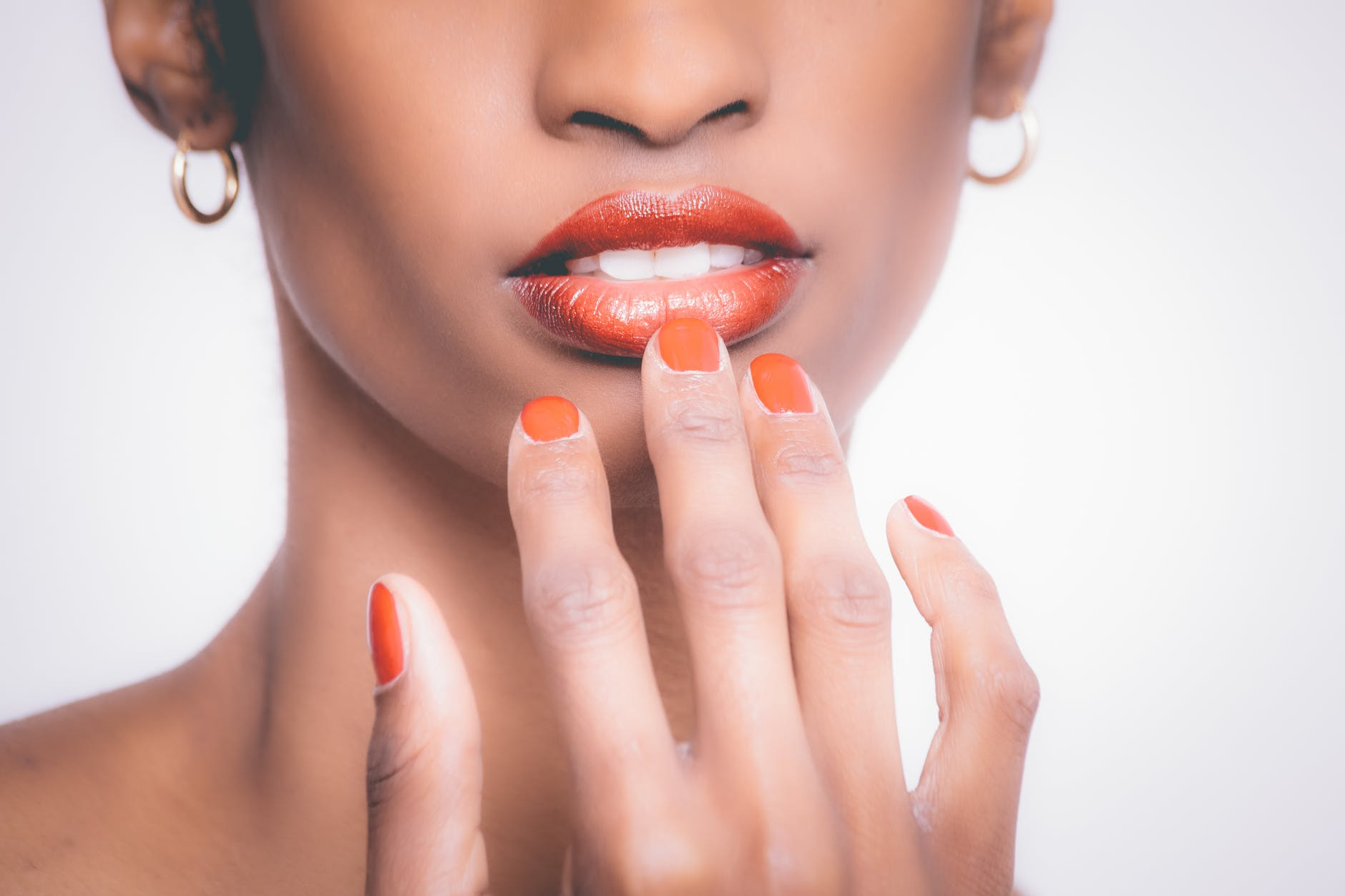 woman with orange manicure